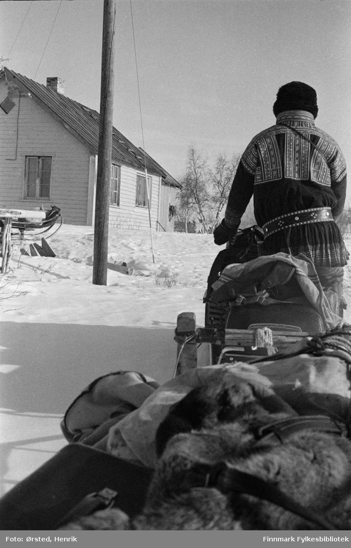 """Postfører Mathis Mathisen Buljo, bedre kjent som """"Post-Mathis"""" i samiske kretser, har kommet frem til en reindriftsenhet for å levere og hente post ute på Finnmarksvidda. På bildet kjører han skuteren mot husene og sleden er fullastet med post, utstyr han trenger på turen og reinskinn.   Fotograf Henrik Ørsteds bilder er tatt langs den 30 mil lange postruta som strakk seg fra Mieronjavre poståpneri til Náhpolsáiva, videre til Bavtajohka, innover til øvre Anárjohka nasjonalpark som grenser til Finland – og ruta dekket nærmere 30 reindriftsenheter. Ørsted fulgte «Post-Mathis», Mathis Mathisen Buljo som dekket et imponerende område med omtrent 30.000 dyr og reingjetere som stadig var ute i terrenget og i forflytning. Dette var landets lengste postrute og postlevering under krevende vær- og føreforhold var beregnet til 2 dager. Bildene gir et unikt innblikk i samisk reindriftskultur på 1970-tallet. Fotograf Henrik Ørsted har donert ca. 1800 negativer og lysbilder til Finnmark Fylkesbibliotek i 2010."""
