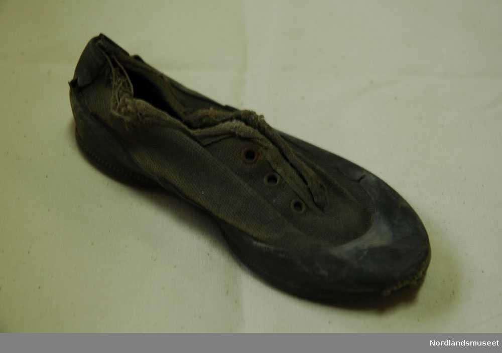 8d8a6f52 Barneskoen er revet opp langs stoffkanten. Skoen har gummisåle under, på  langssiden, oppe. Photo: Nordlandsmuseet