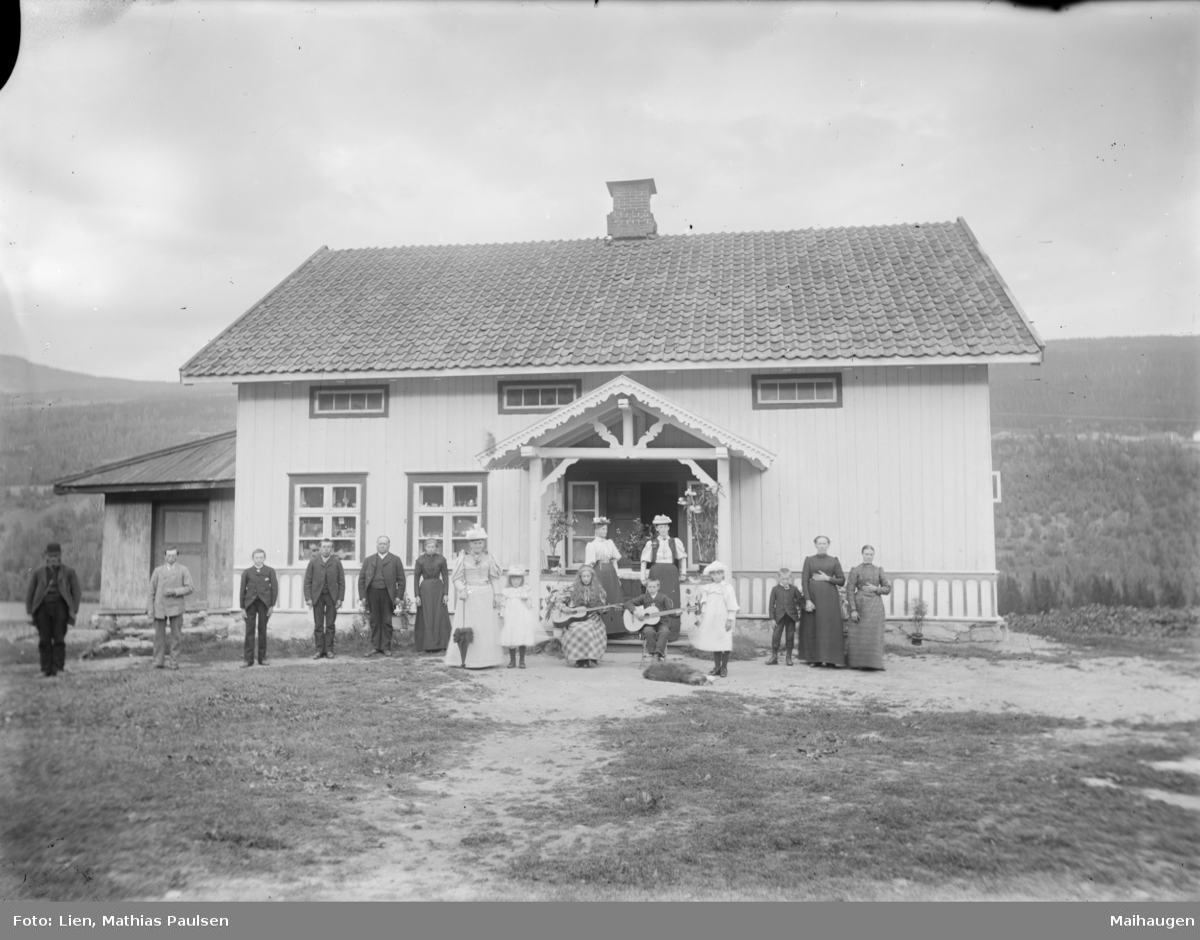 Fåberg, Aurlien, Fram til 1907 var det butikk på Aurlien og ut fra utstillingen i vinduene antas dette å være bygget. 3 generasjoner og antatt tjenestefolk med 16 personer foran hus med 2 barn med gitar.
