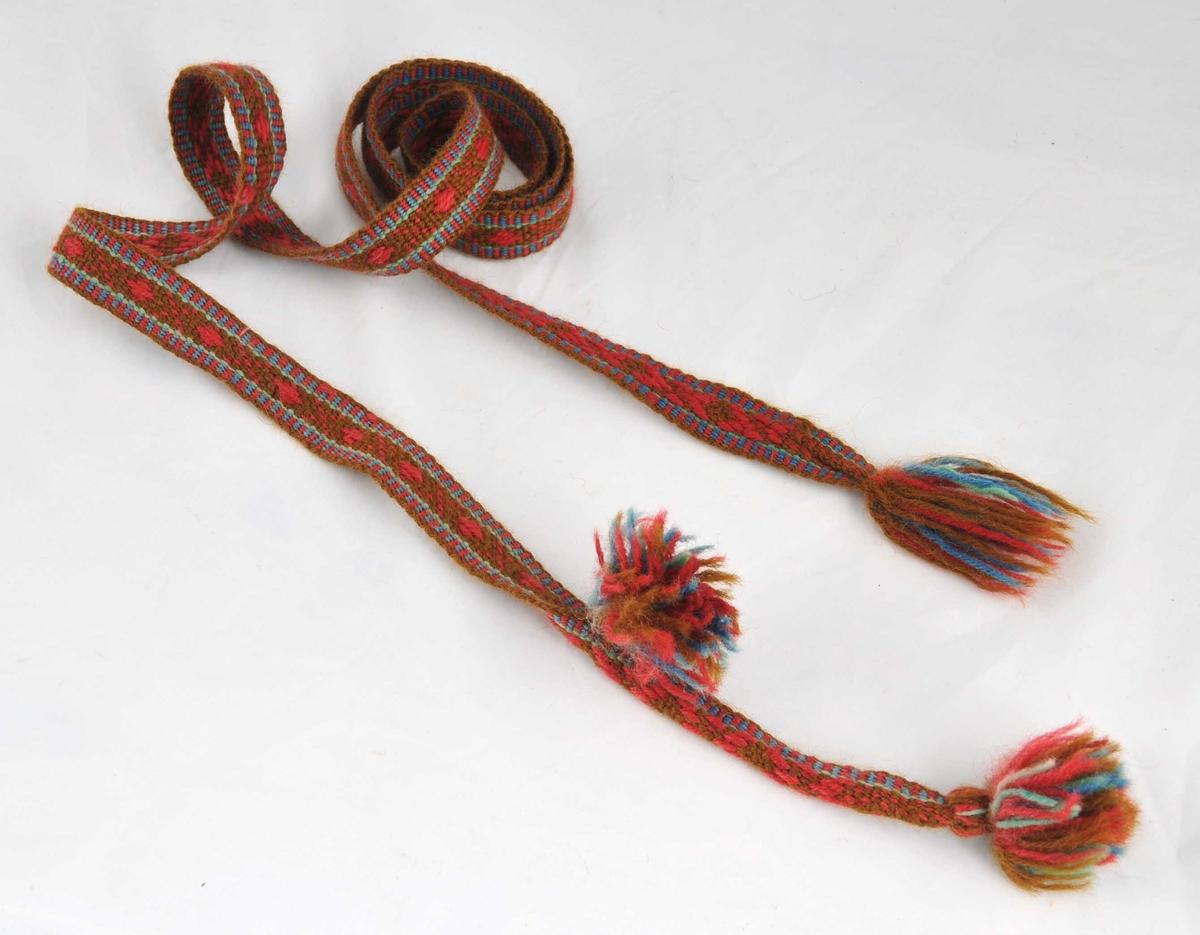 Grindvove band av tynt firetråds ullgarn. 2 dufsar i den eine enden og ein 15 cm. lang ende som er lagd dobbelt og sauma ihop til ein smal tamp. Frynser i andre enden. Bandet brukast til å snøre buksa fast til hudskorne, og den smale enden læser ein det fast med.