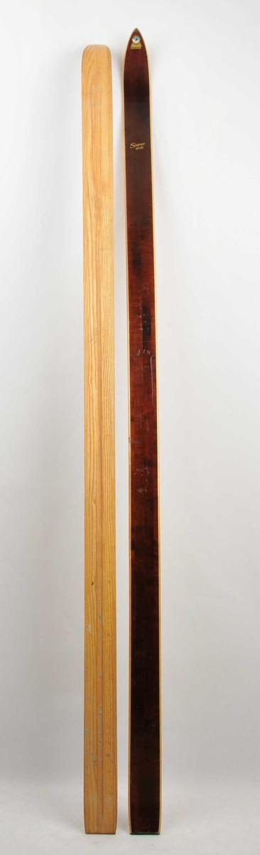 Langrennski for barn laga av tre. Lakkera, med brun overside, trekvite sidekantar og såle. Rønnings emblem med bilete av ein skilaupar på framtupp.