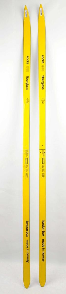 Langrennski laga av glasfiber, gul overside, såle i svart plast. Det har vore bora tre hol til bindingar.