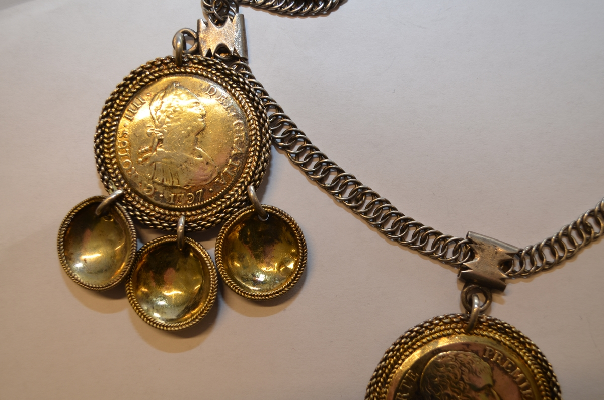 Brudedalar med flatlekkje, med ein fransk og to spanske myntar. Kvar mynt har tre gyldne skåler.