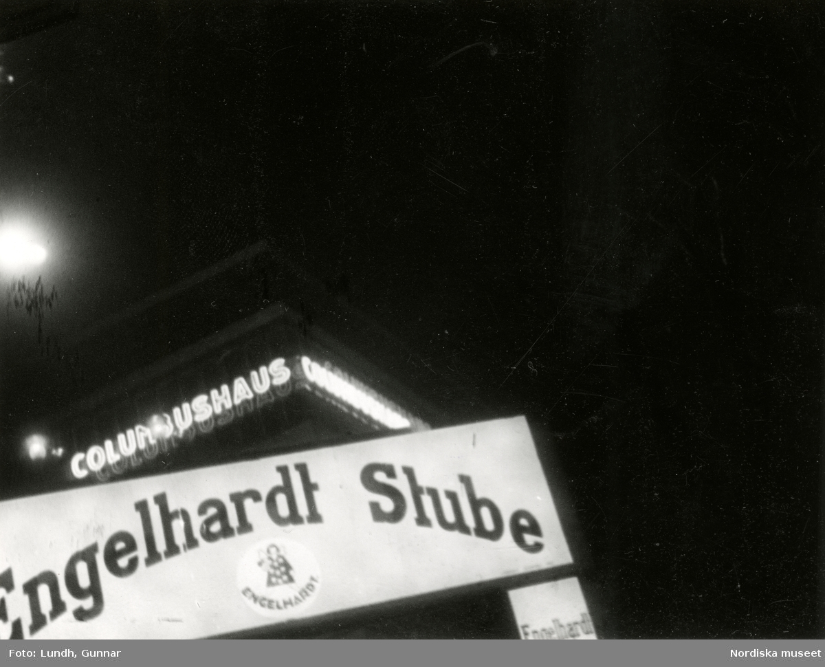 "Potsdamer Platz, Berlin, kvällsbelysning. Ljusskylt med txeten ""Engelhardt Stube"". I bakgrunden kontorsbyggnaden Columbushaus."