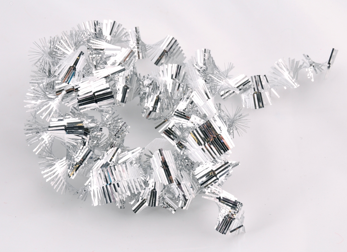 Glitterremse med  sølvfarga remser som er tvinna rundt ein bomullståd, slik at remsene strittar ut og dannar ein spiral.