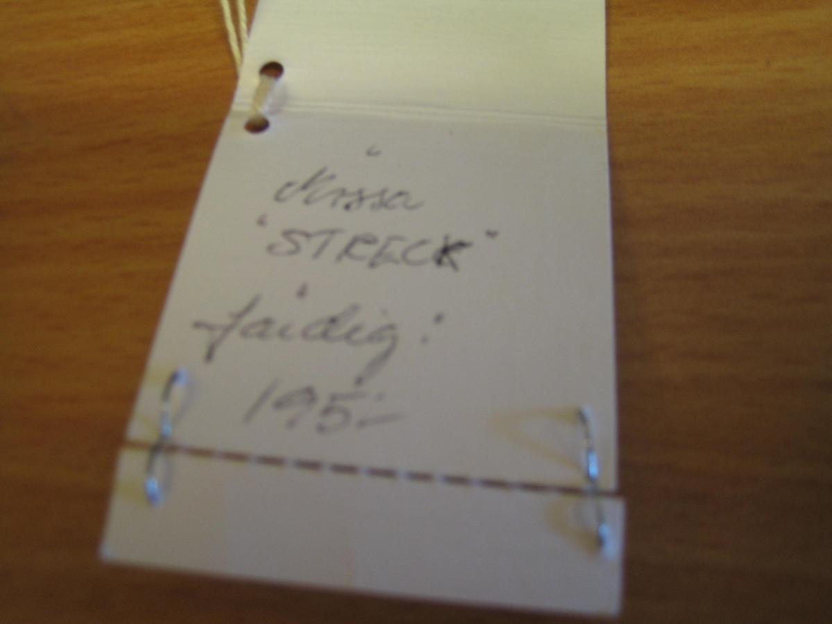 """Mössa i blått och svartvitt flamgarn, slätstickad med rullkant   nertill. En liten stickad topp är också i blått. Avmaskning är gjord på åtta ställen. En lapp är fastsatt med texten: """"Länshemslöjden SKARABORG SKÖVDE"""",""""Slöjdare A-M Nilsson, Material: Ull, Material, Pris: 72:-"""" på ena sidan och """"Mössa STRECK Färdig: 195:-"""" på andra sidan."""