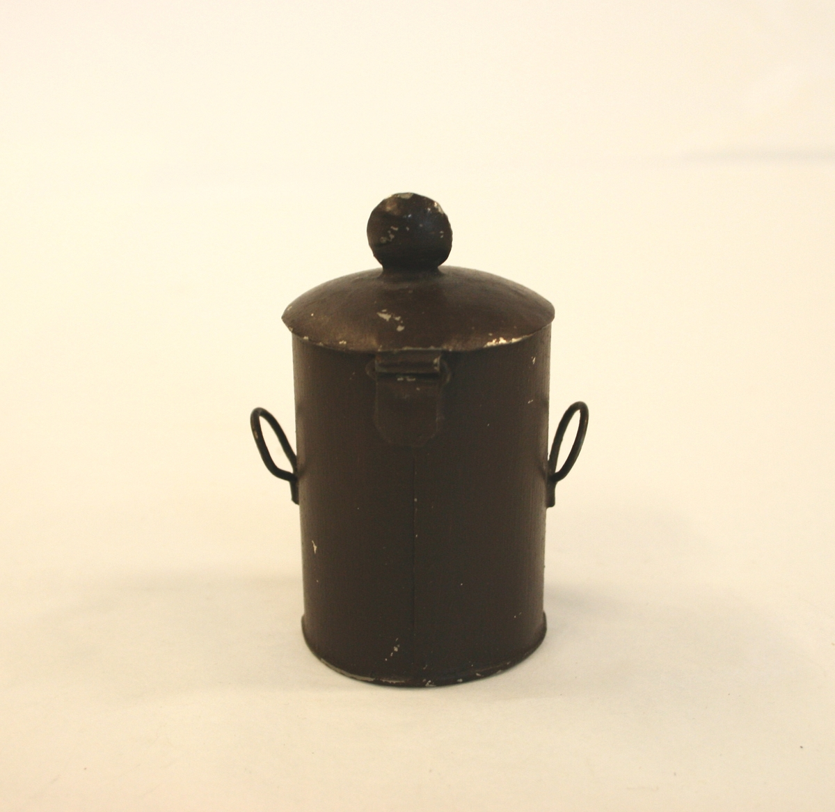 Koksboks med koks.  Sylindrisk formet med åpen luke, to runde hanker på sidene og rund hank på toppen.