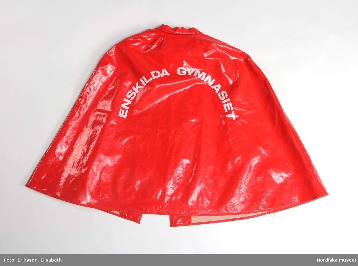 """Cape av röd plast (ev. PVC). Två framstycken, ett bakstycke. Öppen framtill, knäpps i halsen med två blanka tryckknappar. Låg ståndkrage. Slitsar för armar/händer framtill. Ärmhål och kanter kantade med rött textilband. På ryggstycket text i vitt: """"ENSKILDA GYMNASIET"""". Fodrad med vit textil.  Anm. fuktfläckar på fodret. /Leif Wallin 2017-10-17"""