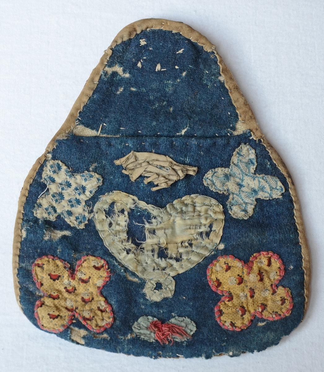 Kjolväska med applikationer av siden och mönstrade bomullstyger på blått ylletygsbotten. Väskan har en baksida av skinn och hake av mässing. Iinsidan är fodrad med grovt linne.