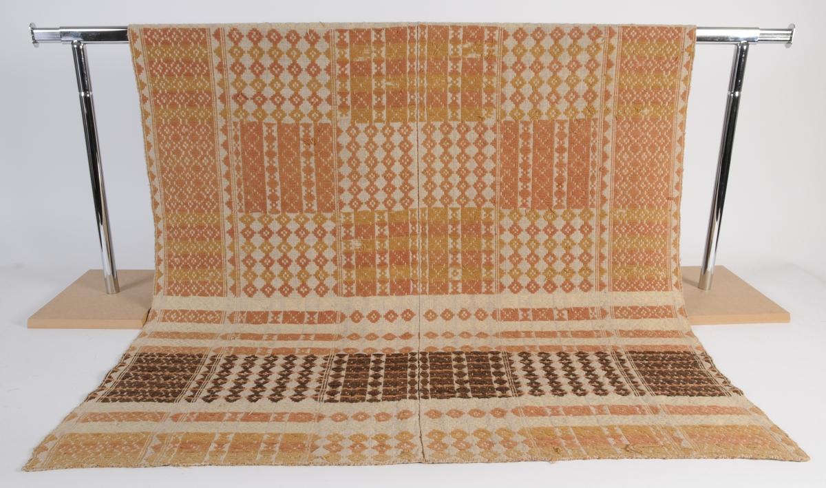 Täcke med mönster i krapprött, svart och gult ullgarn samt hårgarn på linnebotten.