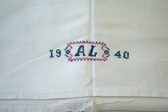 Underlakan av köpt bomullskypert, med broderat monogram i blått och rosa korsstygn.