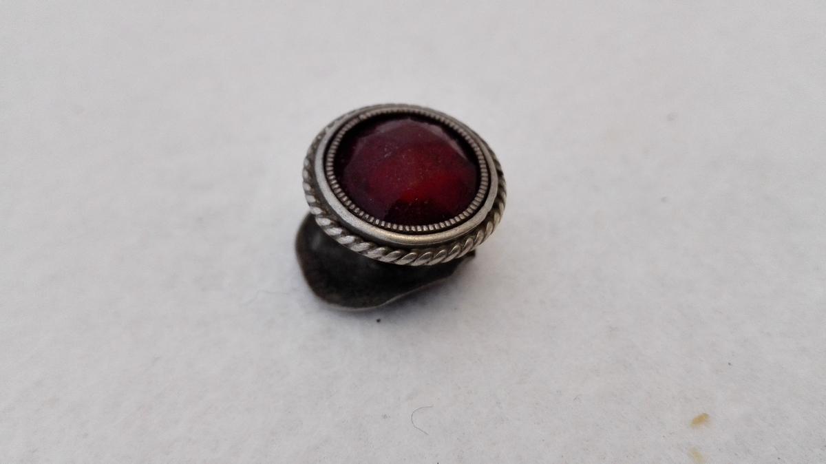 1 kraveknap av sølv med rød sten.  Stetteknap av sølv med rød slepen sten. Underdelen av en gammel sølvmynt. Fra Hafslo. Kjøpt av Jens Skavl, Leikanger.