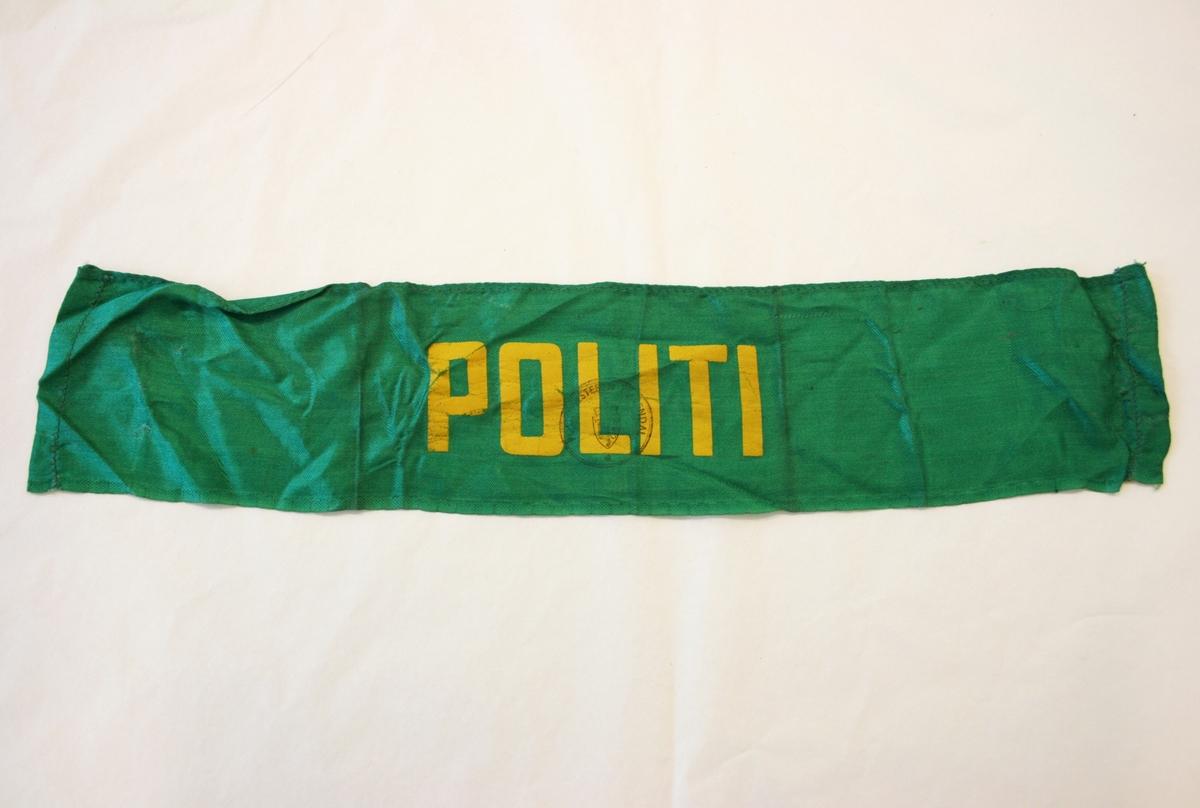 """Armbindet har ordet """"Politi"""" påmalt/påtrykt med gule blokkbokstaver. Oppå bokstavene er det stemplet med stempel fra Politimesteren i Arendal."""