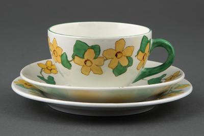 Kopp med tilhørende skål og tallerken, dekorert med gule bekkeblom og blader, utført i dreiet og glassert flintgods for Egersunds Fayancefabrik