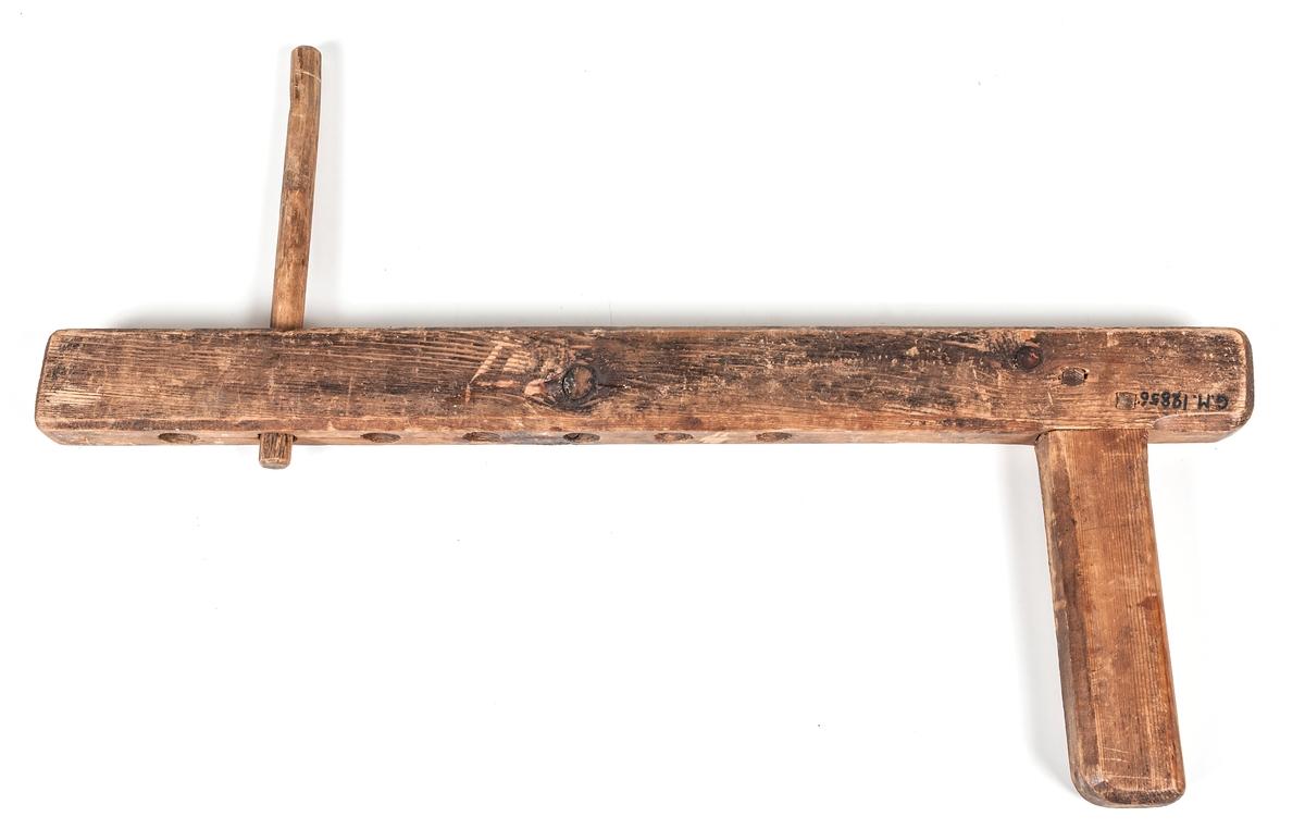 Upptagningsvinda, snörknekt, av trä. En pinne i ett av hålen.