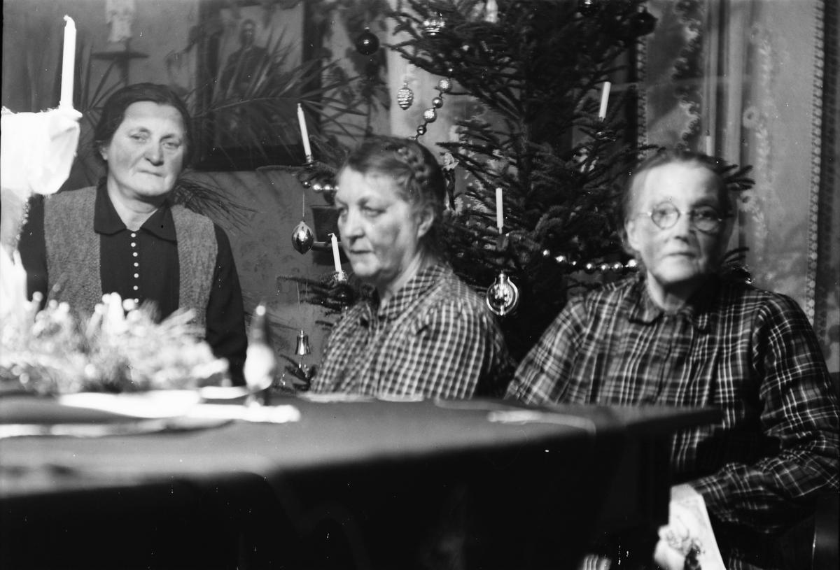 668706710b91 Tre äldre kvinnor vid en julgran i finrummet. Granen är pyntad med levande  ljus,