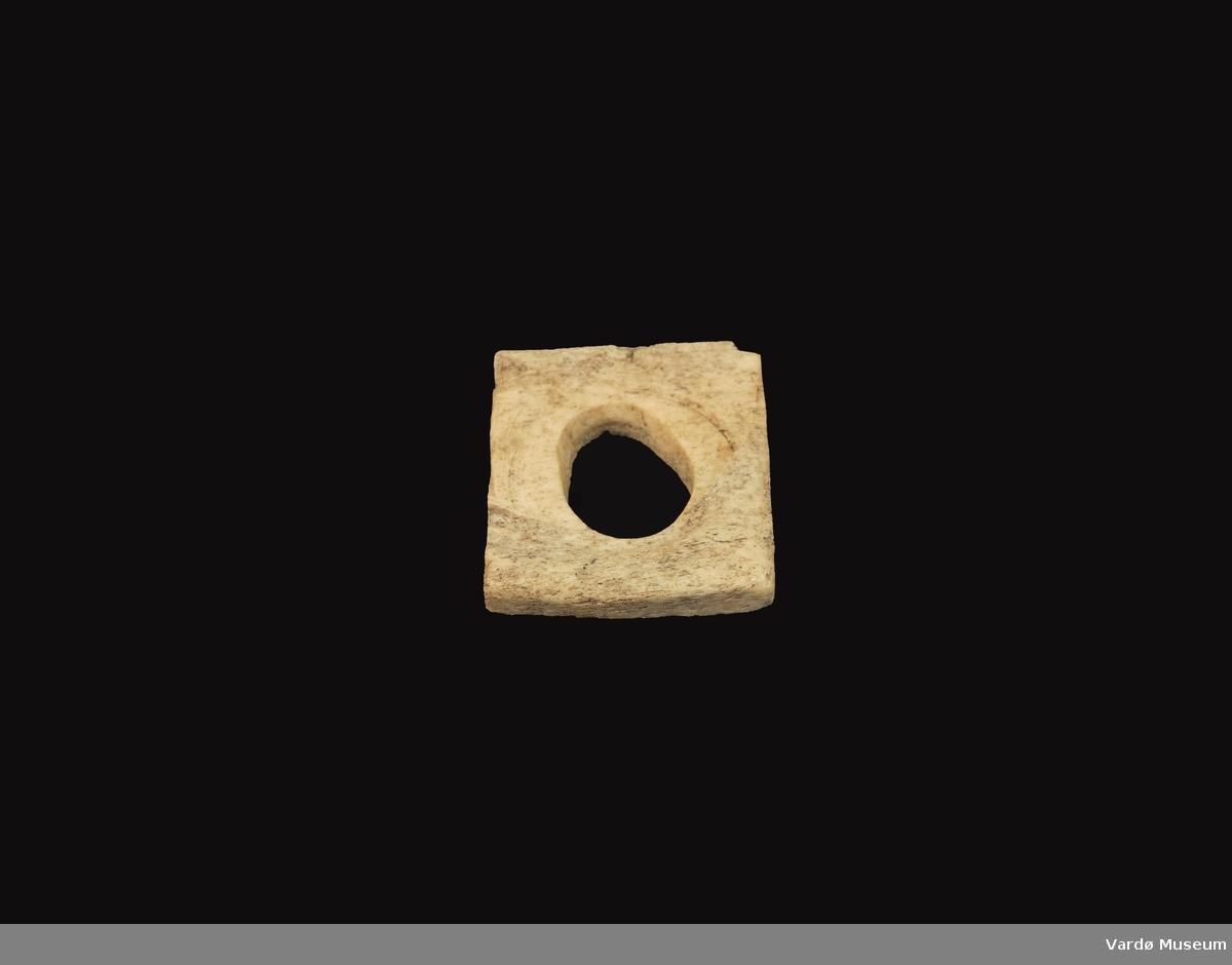 Firkantet og porøs, hull i midten på ca. 2,6 cm i diameter.