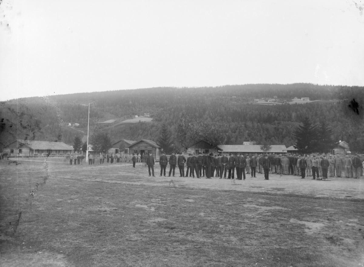Jørstadmoen militærleir med brakker og forlegninger. Samling av soldater og personell med forskjellige uniformer.