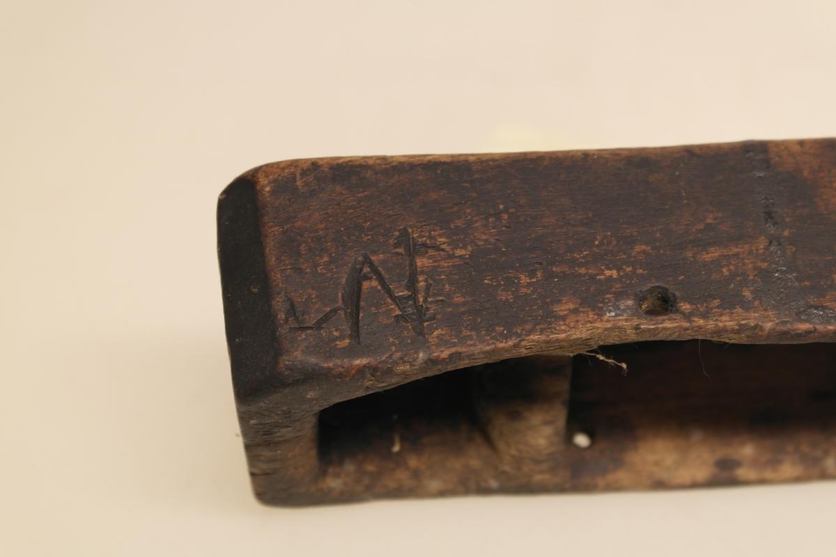 Skrin til fyrtøy i skåret furu. Skrinet er skåret i ett stykke. Det er et stort rom til svovelstikker midt i skrinet, og på hver side er det et lite rom med plass til flint i det ene rommet og knusk i det andre. Avflasset, svart maling. Inngravert en bokstav på siden av skrinet.