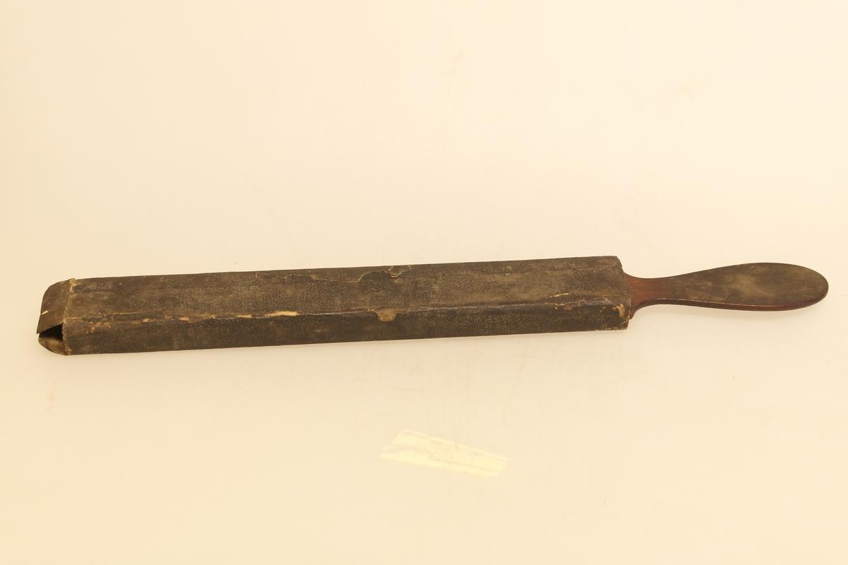 Barberknivsliper (a) med futteral (b).  A) Brynet er laget av tre og lær. Flat, rektangulær form med ovalt håndtak. Treet er kledd med lær på begge sider. Brynet er beiset. B) Eske av papp.