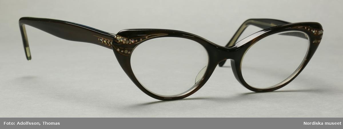 """Ett par glasögon i brun och svart plast med mineralglaslinser (H+0.5, V+0.5). Glasögonen är bruna på framsidan samt på utsidan av skalmarna och svarta på insidan av bågen och skalmarna. Strassdekor på fronten vid gångjärnen samt på skalmarna vid gångjärnen.  På insidan av skalmarna står det instansat """"REVELLEE  U.S.A.  5 1/2"""". På bågens insida står det instansat """"44-20"""". /Petrine Knight, 2014-12-03"""