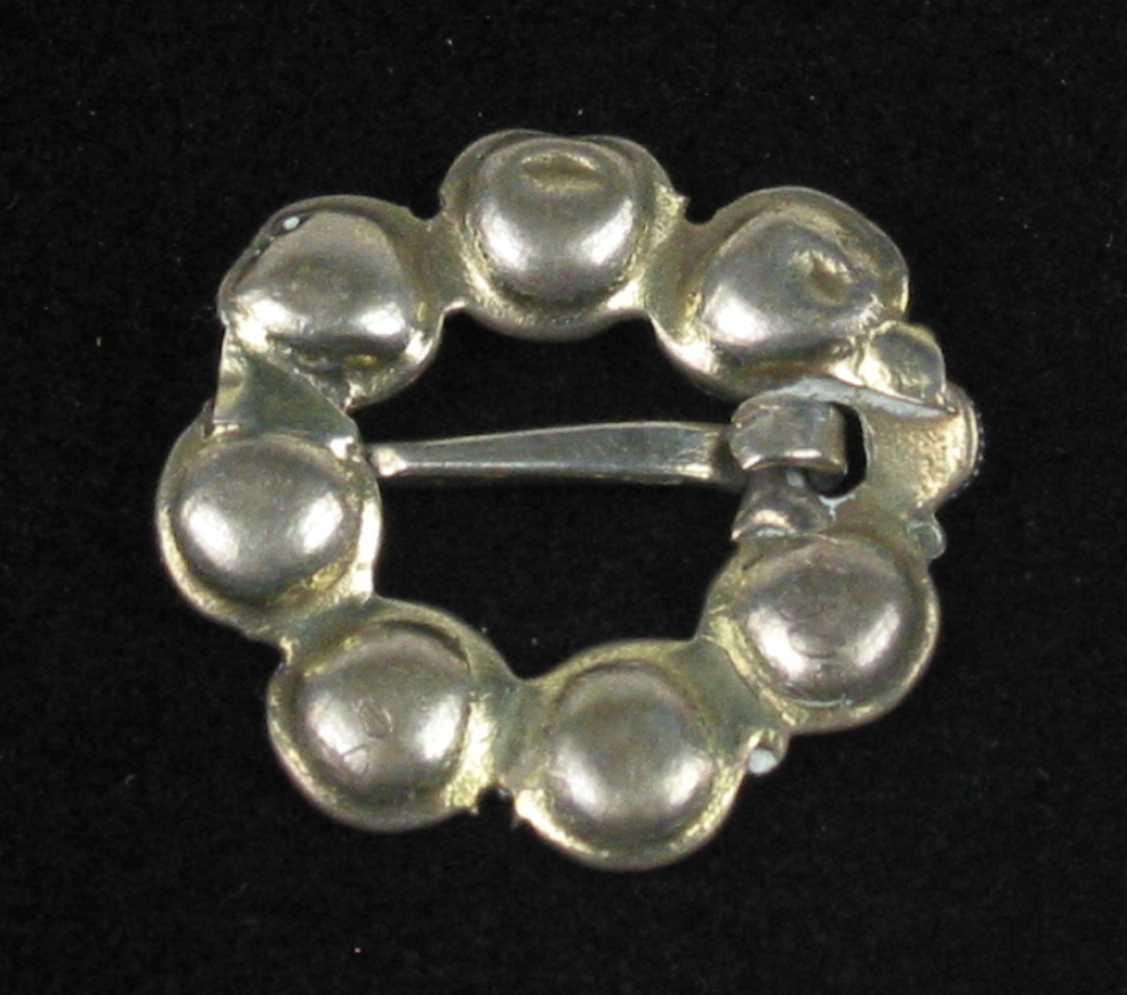 Skålesølje eller øyesølje i sølv med syv drevne skåler kantet med tvinnetrådsring. Gjord og tornring mangler, men bak tornfestet er det pålagt en knoppkruse.