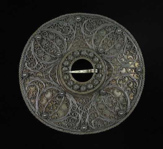 Trandeimssølje i sølv med hel, nesten plan bunnplate. En krusebole i midten ... tornhullet. Bolens kantbånd og tornring er av flettetrådsbånd. Kruseringen mellom dem består av femten knoppkruser med perlefyll i krusehjørnene. Bak tornfestet er to paralelle stykker krusetråd brukt som fyllmotiv. Ved foten av krusebolen er det lagt en rørtrådsring av samme form som gjorden og mellom disse er bunnplata prydet med tråd i rosemønster. Plata har ellers en indre og en ytre krusering på henholdsvis fire og åtte perlekruser. Hver kruse er festet med en splitt på baksida av plata. Bunnmønsteret er sammensatt av fire like deler som ligner blomster; rose eller et bladnyre.