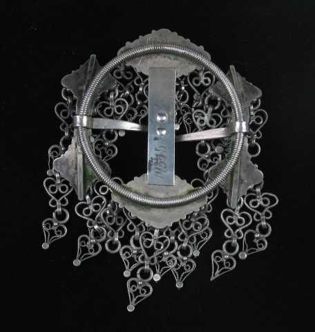 Hornring i sølv med midtkavl og to motstående torner. Ringen er av skruetråd. Stolpene er hjerteformet i endene med perlekruser og perlefyll. Fra krusen i hver av stolpehjertets tre ender går det ut en løkke som bærer trådvedhenget. Det består av tre sammenlenkede deler: Nærmest løkka er det en liten glatt ring, så følger en hekteformet trådring sammensatt av to s-formede tråder og ytterst et trådformet hjerte med filigransmønster inni. Ytterst på hjertespissen er det en knupp. Midtkavlen er den bred flat plate loddet innpå midthornene. På forsiden er den kantet med en dobbel tvinnetråd på hver side, og midtfeltet er belagt med perlekruser. I hjørnene er det perlefyll. Midthornene er småtunget og tett belagt med perlekruser. På seks av de seksten krusene er perlene erstattet av en løkke som bærer dingelet. Begge tornene har v-formet strekdekor.