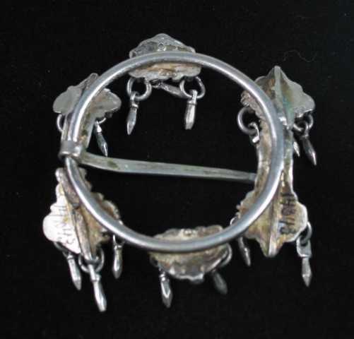 """Hornring i sølv med byggkorndingel. Ringen ser ut til å være støpt rørtrådsformet. Stolpene eller hornene har perlekruser. Endene er hjerteformet med fire kruser og en plate i midten. I stedet for perler har det tre ytterste krusene en ringbærende løkke. I hver ring henger et lite""""byggkorn"""". Mellom stolpene er det en liten krusebelagt plate omtrent av form som et segment. Tre byggkorn er festet til platen som på samme måte som på stolpene. Ingen synlige stempel."""