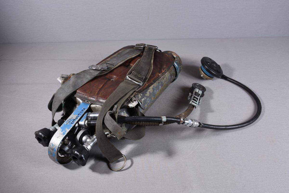 To stål luftflasker med slange for tilkopling til maske og til trykkmåler. Flaskene har ventiler og koblinger i enden. Polstret bæremeis med seler.