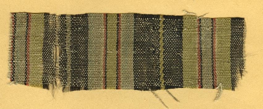 Anmärkningar: Vävnadsprov Olga Anderzons samling. Fru Elna Johansson, Nässelbo Möklinta. Vävprov av halvylle i tuskaft, randigt. Varpen av bomull är i beigt. Inslaget av ull är randat i svart, ljusgrönt och rött. L. 1450 1430 Br. 470 500