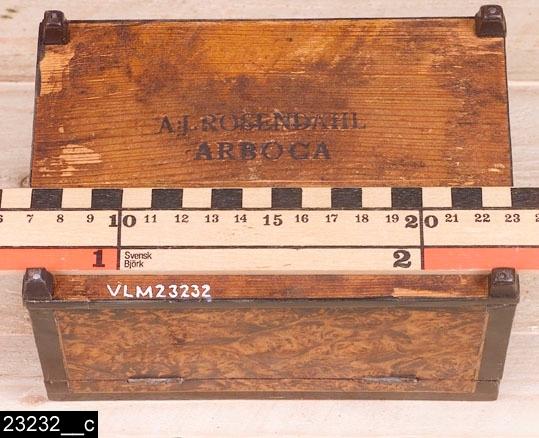 """Anmärkningar: Schatull, Anders Jacob Rosendahl, 1784-1836.  Gångjärnsförsett rektangulärt lock med ett silverhandtag. Handtaget är försett med fyra olika stämplar (bild 23232__b). Den första (från vänster) anger att handtaget är gjort av Carl Fredrik Seseman (om honom se nedan). Den andra stämpeln, en örn, är en stämpel för Arboga stad. Den tredje stämpeln (H2) är en årsstämpel och betyder 1790. Den fjärde stämpeln med tre kronor (kattfoten kallad) är en kontrollstämpel som anger att silverhalten är kontrollerad. Undertill är schatullet försett med stämpeln """"A:J. ROSENDAHL /  ARBOGA"""" (bild 23232__c). Invändigt är schatullet klätt med rosa papper (bild 23232__d). Fyra nedåt avsmalnande små fötter. H:92 Br:161 Dj:108  Hela schatullet är fanerat med alrot, blindträet är furu. Kanterna är svärtade. Bild 23232__e visar bild på nyckeln, möjligen är den av silver. I dess innerkant finns en otydlig stämpel som kan tolkas som en kontrollstämpel (tre kronor).  Mälardalen och framför allt städerna Arboga, Köping, Kungsör och Eskilstuna var under 1700-talets senare hälft och början av 1800-talet centrum för tillverkning av alrotsfanerade möbler och föremål. Här tillverkades bl.a. fällbord, byråar och olika sorters askar. Föremålen såldes inte bara inom mälardalen utan även till Stockholm och till andra länder. Det främsta namnet inom alrotsföremålsproduktionen är Jacob Sjölin (1737-1785). Alroten togs inte från alens rötter utan från stamansvällningar vid rötterna. I synnerhet vid Mälarens stränder har tillgången på detta sorts virke varit god. På slottet förvaras en kortkatalog, upprättad av f.d. antikvarie Carin Thorsén. Den upptar över 300 alrotsföremål tillhörande museer, privatpersoner etc.  Anders Jacob Rosendahl (1762-1836), mästare i Arboga snickarämbete 1784 (troligen), verksam till sin död. 1786 blev Rosendahl ålderman i Arboga snickarämbete, osäkert hur länge han behöll den positionen. Rosendahl gifte sig 1786 med Catharina Nordling som var änka efter Jonas Nordling """