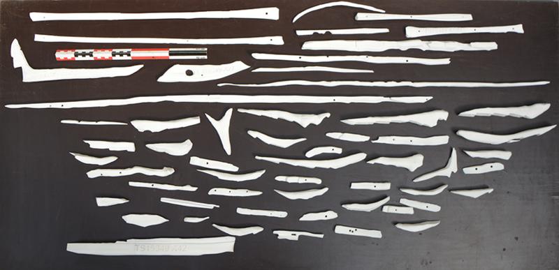 Oversiktsbilde av de 3D-printede delene til modellen av Lovundbåten. Små båtdeler i hvit plast ligger spredt ut på et bord. (Foto/Photo)