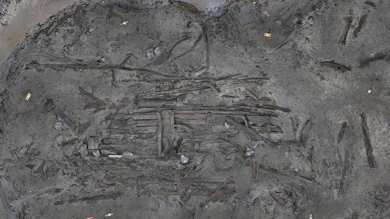 Bilde i fugleperspektiv av vraket av Lovundbåten.  De sammenhengende delene av vraket i midten av bildet er omgitt av en rekke løsrevne deler spredt ut over den midlertidig tørrlagte sjøbunnen.