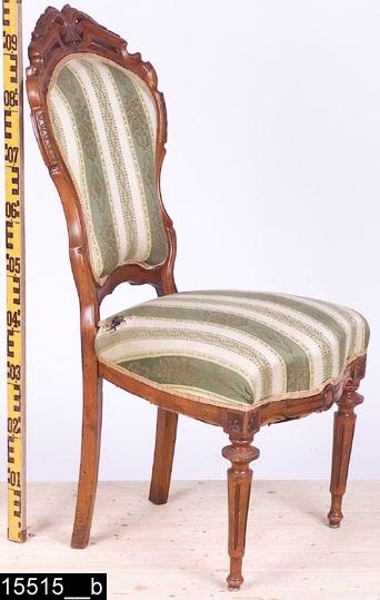 Anmärkningar: Stol, nyrokoko/Louis seize stil, omkring 1900.  Genombrutet överstycke med skuren dekor och ett krön i form av skurna akantusblad (bild 15515_2__c). S-svängda och konturerade bakstolpar med zig-zagmönstrad karvsnittsdekor (bild 15515_2__b och c). En kontursågad ryggslå. Stoppad sits och rygg med randigt och mönstrat sidentyg. Sitsen är också fjädrad. Framsarg med bland annat kannelyrliknande skuren dekor och stiliserad medaljong i mitten (bild 15515_2__e). Båda framben är vardera försedda med två skurna rosettanfanger (bild 15515_2__d). Frambenen är också profilsvarvade och kannelerade. H:970 Br:455 Dj:535  Stolen är troligen gjord av valnöt, möjligen mahogny. Den har försetts med någon typ av ytbehandling (vilken gör att bilderna är starkt glansiga).  Tillstånd: Skada på tyget på sitsen. Frambenens fotavslutningar i stål är senare.  Historik: Gåva juni 1970 av fam. Regnfors, Betels skola, Skultuna.
