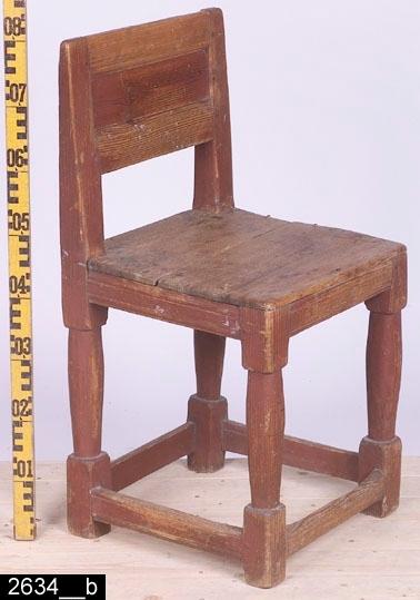 Anmärkningar: Stol, s.k. åttaslåstol (benämning efter antalet benslåar), 1800-talets första hälft.  Rektangulär ryggbricka med profilerade slåar upptill och nedtill. Raka bakstolpar. Sits av trä. Fyra sargar som är profilerade i nederkant. Fotslåarna är  profilerade i över- och nederkanterna. Fyra balusterformade ben med fyrkantiga fotavslutningar (bild 2634__b). H:800 Br:405 Dj:420  Hela stolen är mörkröd och bär spår av naturligt slitage. Den främre fotslån är nött efter lång tids användande.  Invnr. 2634 bestod ursprungligen av två stolar. På stol nummer 2 är namnet August målat på ryggstödets bricka. I samband med stiftelseupplösningen 2005 överläts stolen med August på ryggbrickan till Vallby Friluftsmuseum. Den andra stolen finns nämnd i 2003 års inventarieförteckningen över Vallby.  Tillstånd: Sitsen är lös.  Historik: Gåva av fröknarna Behm, Västerås.