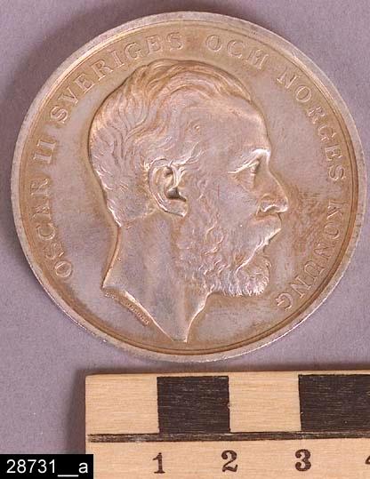 """Anmärkningar: Mynt, 1881.  Runt mynt. På den ena sidan finns en bild föreställande Oscar II samt texten """"OSCAR II SVERIGES OCH NORGES KONUNG"""" (bild 28731__a). På den andra sidan finns en bild föreställande ett skyddshelgeon / en segergudinna samt diverse industriattribut. Där finns också följande text """"INDUSTRI OCH SLÖJDUTSTÄLLNINGEN I MALMÖ 1881"""" samt """"LEA AHLBORN"""" (bild 28731__b). Br:3 D:50  Historik: Gåva från SAPA AB, Division Service, 2002. Föremålet stod i ett skyddsrum på bruksområdet i Skultuna."""