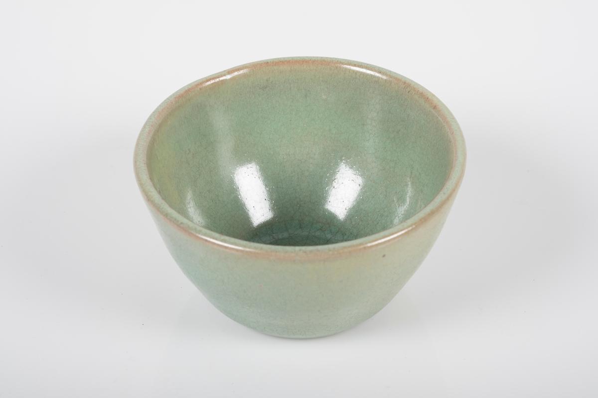 Rund kopp i keramikk med grønn lasur. Buet hank på koppen. Tre små knotter på undersiden av koppen, usikker funksjon.