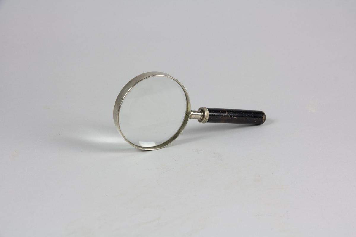 Förstoringsglas bestående av cirkelrunt förstorande glas infattat i vitmetall och skaft av svartmålat trä.