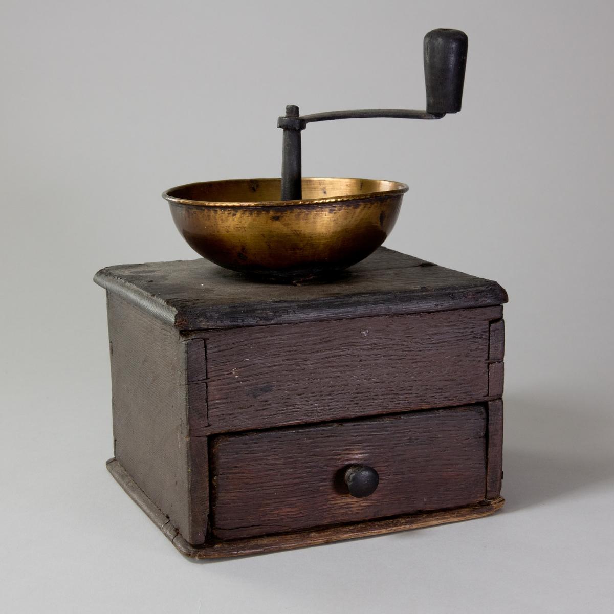 Kaffekvarn av ek, kvadratisk med låda. Ovanpå lådan skål av mässing med hål och horisontell vev av järn och trä.