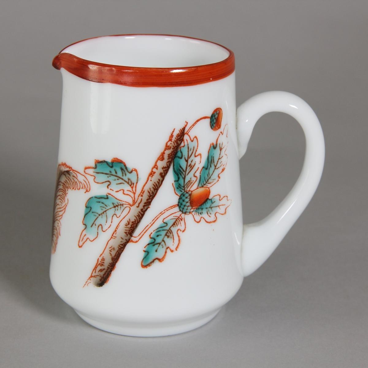 Gräddkanna av glas, vitt med målad dekor i form av ekollonkvist och ekorre i rött, brunt och turkos. Rödmålad mynningskant.