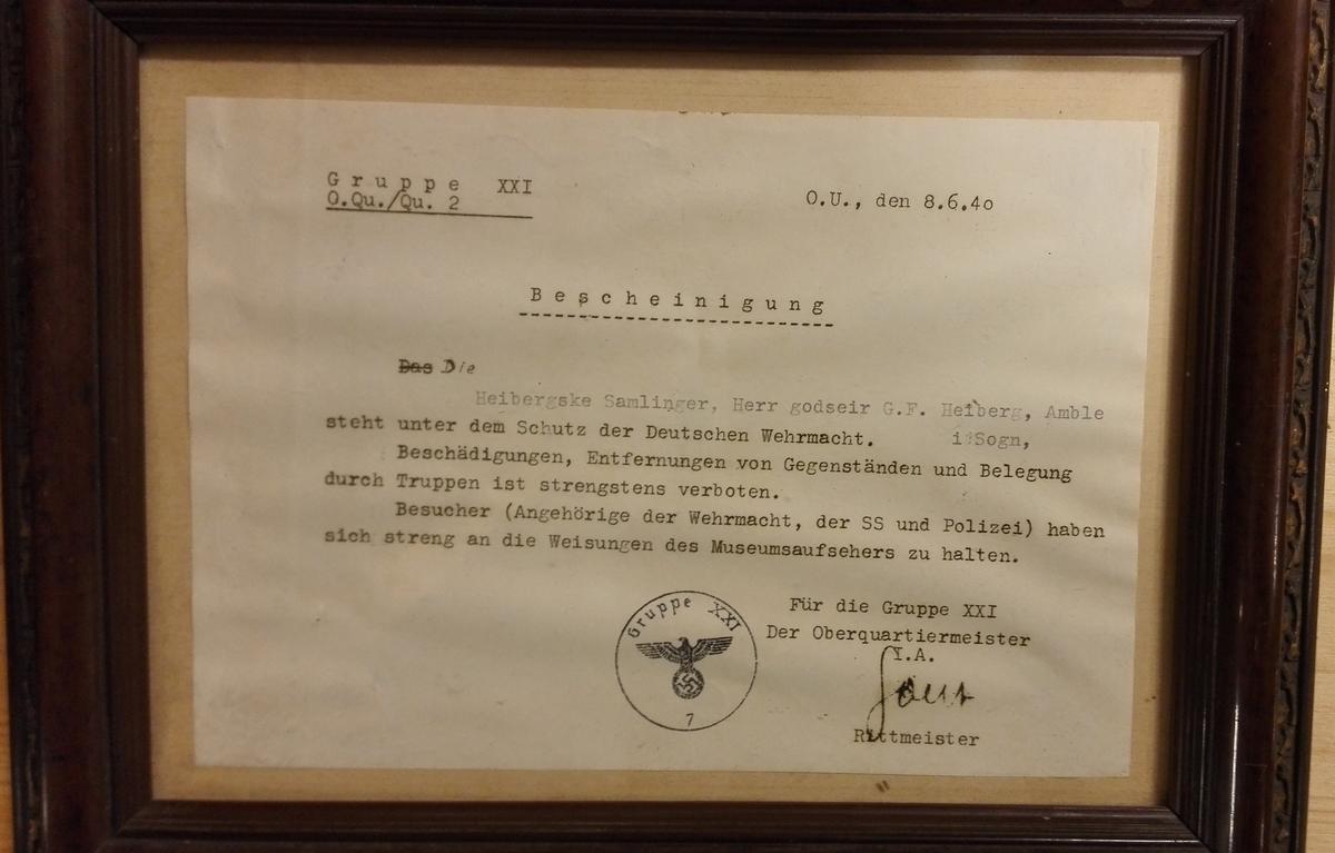 Erklæring frå denb tyske okkupasjosmakta om at De Heibergske Samlinger står under beskyttelse av den tyske okkupasjonsmakta og at all skade på musee og museumsgjenstandar er srengt forbode. Alle - også okkupasjonsmakta skal retta seg etter museumsperonalet sine anvisningar.  Dokumentet er skrive på tysk, stempla og signert  Det innramma i brun treramme med gulldekor.
