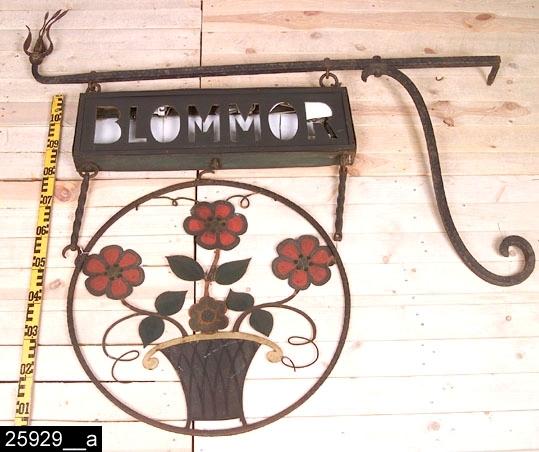 """Anmärkningar: Skylt, 1900-tal.  Skylten består av en konsoldel med vågrät överliggare med en S-sväng järndel längst ut åt det ena hållet, åt det andra hållet finns en blomkrona. I konsolen hänger det en ljusskylt med texten """"BLOMMOR"""". Här står också med mindre och svagt upphöjd stil, """"AB Roos Skyltreklam"""" (bild 25929__b). I ljusskylten hänger det från spiralvridna järnhängare en rund skylt med en målad blomstersiluett som stiger upp ur en kruka. H:1440 L:1510  Tillstånd: Glaset i ljusskylten är skadat och delvis borta. Delar av bokstäverna i ljuslyktan är borta eller lösa. Ett blad i kronan är av. En krok är av."""