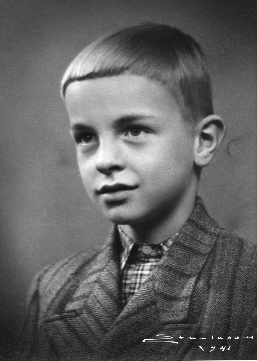 Portrett av ung gutt. Han har tweed-jakke og rutete skjorte.