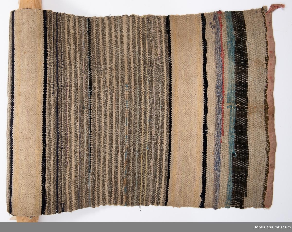 Tvärrandig. Ca 40 cm breda smalrandiga partier med omväxlande två mörka och två ljusa inslag. Mellan de breda partierna finns ca 13 cm breda ljusa partier. Färger i de breda partierna: Grått, mörkblått, svart omväxlande med beige, ljusgrått, ljusblått. Färger i de ljusa partierna: Gulbeige, svagt rosa. Kortsidorna kantade med remsor av kypertvävt bomullstyg, nu svagt rosa från början rött. Blekt, smutsig, hål och brustna trådar i ena kanten, ytterligare små bristningar här och var.  Ingår i föremålssamling ur sjöbod från Hällsö, Havstenssund, Tanum sn. Se UM017521