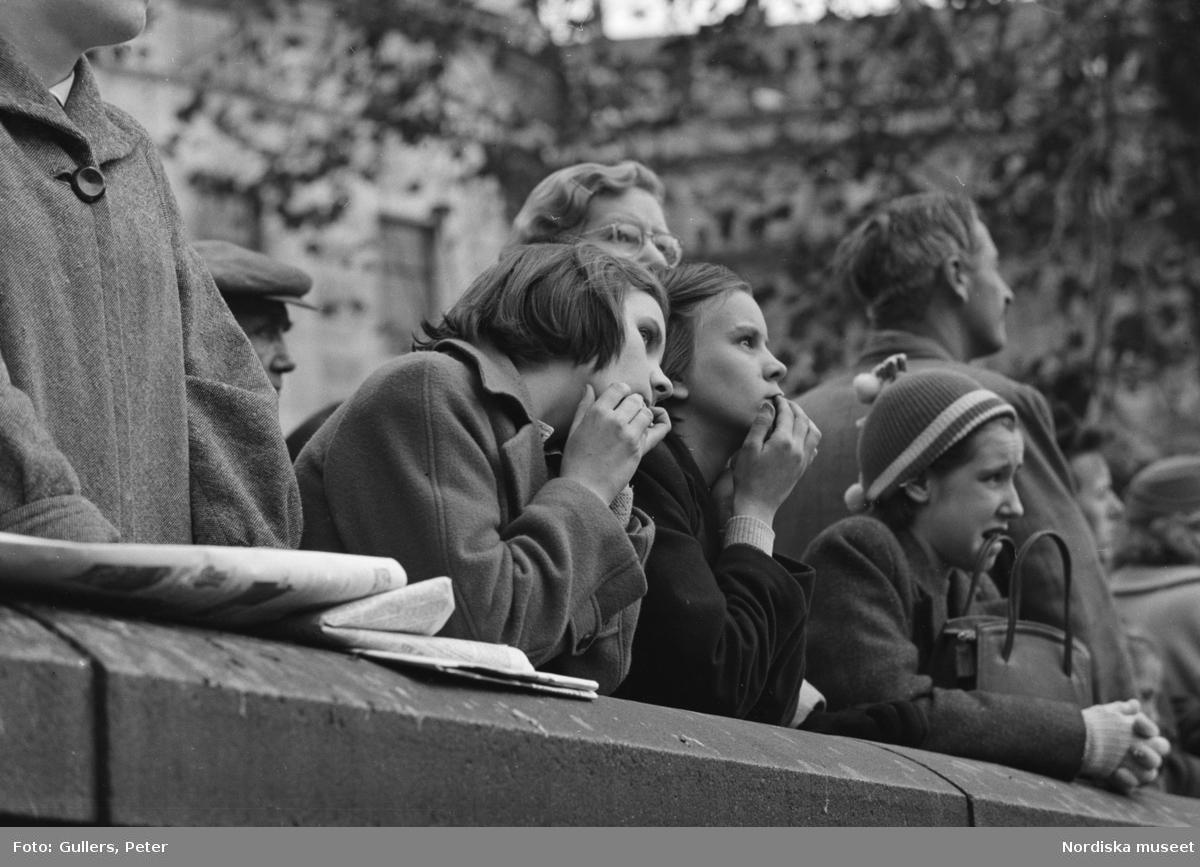 London. Folksamling, unga kvinnor lutar sig mot en mur.