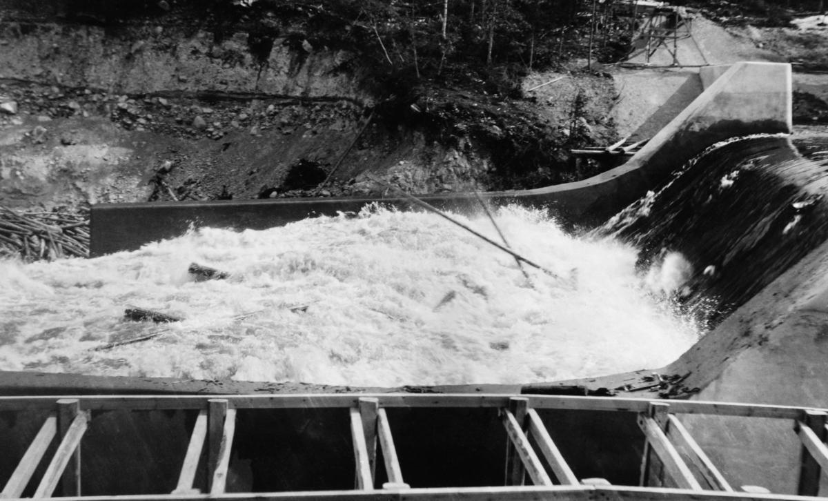 Den såkalte «Nydammen» i elva Søndre Osa i Åmot i Hedmark.  Her ble det i perioden 1912-1914 bygd et for sin tid stort kraftverk som skulle utnytte energien i Osfallet.  Dammen som magasinerte vann til dette kraftverket brast under en plutselig vårflom i 1916, som forårsaket betydelige skader.  Den opprinnelige dammen lot seg ikke gjenoppbygge.  I stedet ble det oppsatt en ny dam i det nye løpet som vannmassene fra dambruddet hadde skapt.  Denne dammen var en betongkonstruksjon.  På dette fotografiet ser vi hvordan vannet, etter å ha passert damkrona, dannet en kvitskummende masse over ei «golving» nedenfor fallet.  I disse kvitskummende vannmassene skimter vi en del fløtingstømmer.  I forgrunnen skimtes en del trekonstruksjoner i noe som later til å ha vært en kanal ved siden av tømmerløpet.  Dette kan ha vært ei fisketrapp.