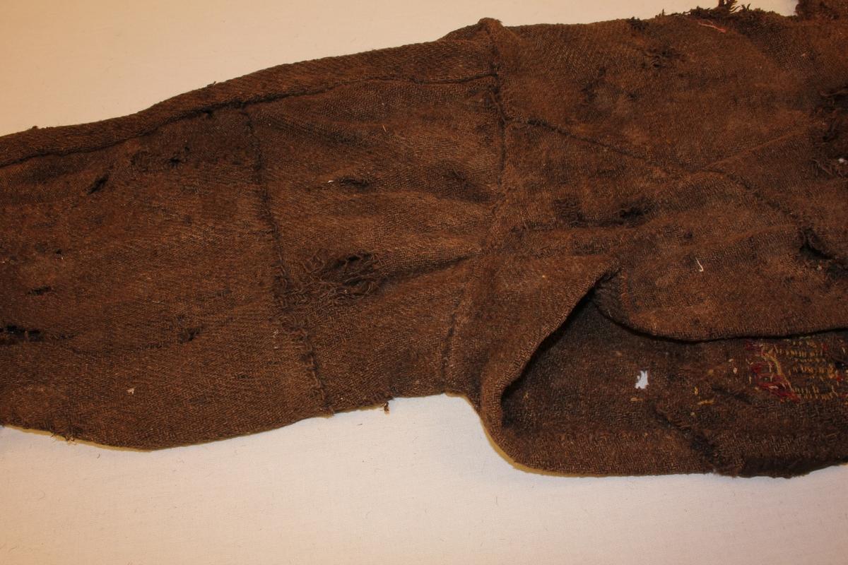 Ei side av jakke av brun vadmål. Handsauma skøytar. Svært slitt.