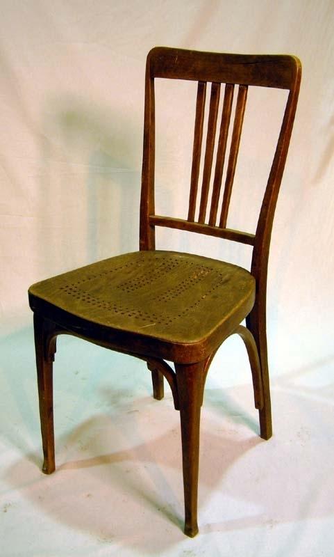 """Stol helt i trä. Fyra ben, släta, bakbenen svagt bakåtböjda, nedtill på frambenen lökformade ansvällningar. Tvärslåar mellan varje ben i form av fastskruvade kraftigt böjda ribbor. Sits av plywood perforerad med hål som bildar enkla mönster. I ryggstödet mellan en tvärslå och ryggstödets överliggare, fyra stycken lodrätt stående ribbor. På sargens en insida en klisterlapp med tryckt text som anger stolens tillverkare och tillverkningsort: """"Thonet. Wien"""" samt en logotyp med bokstäverna G och T liggande omlott inom en cirkel. På annan insida av sargen stämplat """"Thonet""""."""
