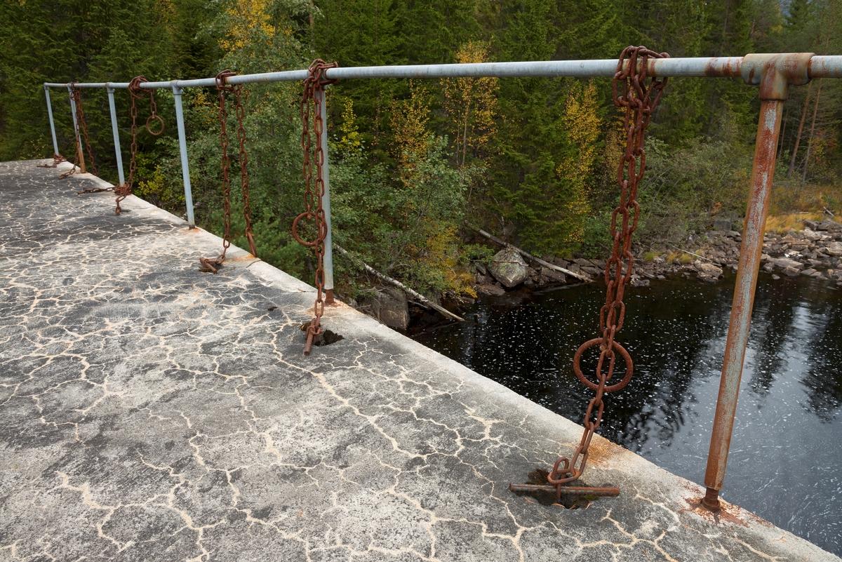 Detalj fra fløtingsdammen ved utløpet av Nedre Bjørvatn eller Nedre Bjorvatn [navneform brukt i dokumenter fram til midten av 1900-tallet] i Tinn i Øst-Telemark.  Den nedre Bjørvassdammen befinner seg høyt oppe i den fløtbare delen av Rauavassdraget.  Flere damkonstruksjoner har avløst hverandre på dette stedet.  Den siste ble støpt i 1962, som en såkalt «kvan-dam», med stålluker fra Foss bruk i Sande.  Fotografiet viser hvordan kjetting fra nederkanten av stållukene ble ført gjennom hull i den støpte brua, der det ble stukket jernteiner gjennom lekker i løftekjettingen når lukene sto i ønsket posisjon.  Løskjettingen ovenfor dette festepunktet ble knyttet fast til det galvaniserte jernrekkverket ved bruas ytterkant.  I bakgrunnen ser vi noe av vassdraget.